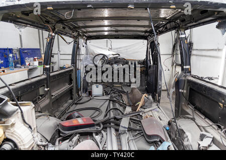 Car interior in the back of a van with a disassembled lining, seats removed, spare parts lying on the floor glass and rubber seal during preparation i - Stock Photo
