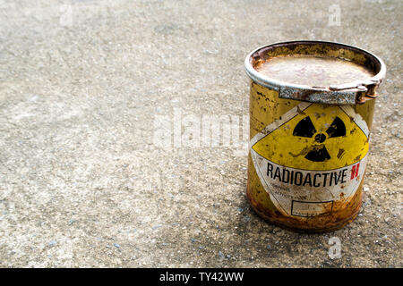 Radiation warning sign on a rusty package of the radioactive material container on the rough concrete floor - Stock Photo