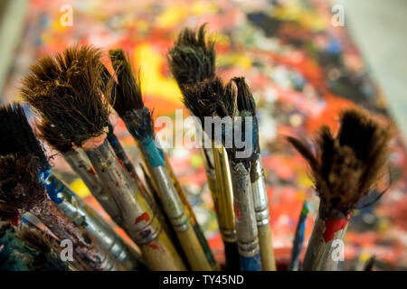 Many old paintbrushes on artwork table Stock Photo