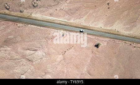 Single car on an old Desert road, Aerial follow image. - Stock Photo