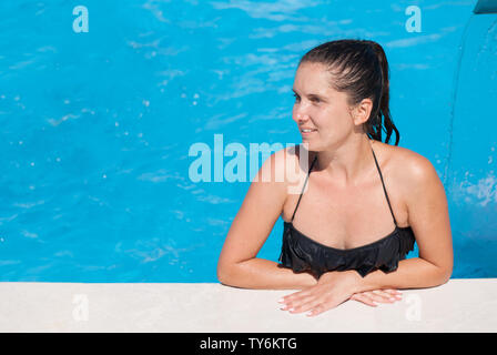 beautiful happy young woman wearing swimsuit sunbathing in turquoise swimming pool during summer leisure vacation - Stock Photo