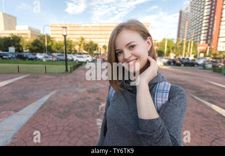 Portrait of young smiling caucasian woman traveller with backpack - Stock Photo