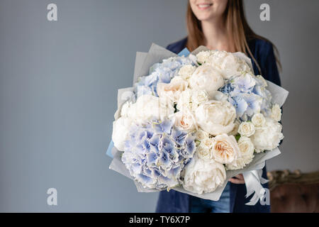 White peonies and blue hydrangea. Beautiful bouquet of mixed flowers in woman hand. Floral shop concept . Handsome fresh bouquet. Flowers delivery