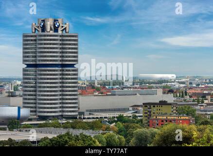 The tower of the BMW (BMW-Vierzylinder or BMW-Turm), in the background the Allianz Arena, soccer stadium. Munich, Germani, Bavaria, Europe - Stock Photo