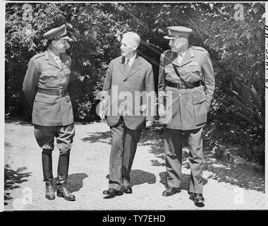 L to R: Field Marshall Sir Harold Alexander, Supreme Commander MTO, Secretary of War Henry Stimson, and Field Marshall Sir Henry Maitland Wilson, Chief of British Staff Mission in Washington, are chatting in the garden of Mr. Stimson's house in the Potsdam Conference area in Germany. The Field Marshalls are luncheon guests. - Stock Photo