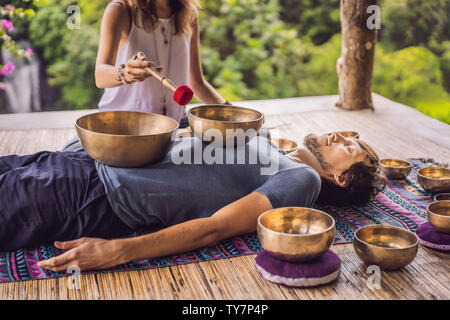 Nepal Buddha copper singing bowl at spa salon. Young beautiful man doing massage therapy singing bowls in the Spa against a waterfall. Sound therapy - Stock Photo