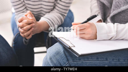 Psychiatrist taking notes during group therapy of support group - Stock Photo