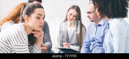 Sad lonely woman sitting at support group session - Stock Photo