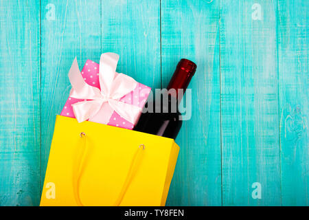 a bottle of wine in a yellow package as a gift, next flowers, gifts, copy space, on blue wooden background, to give girls a set of gentlemen for Datin - Stock Photo