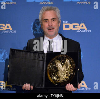 Alfonso Cuaron (C) appears in the press room with actresses Marina