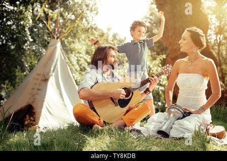 Pleasant nice man playing songs for his family - Stock Photo