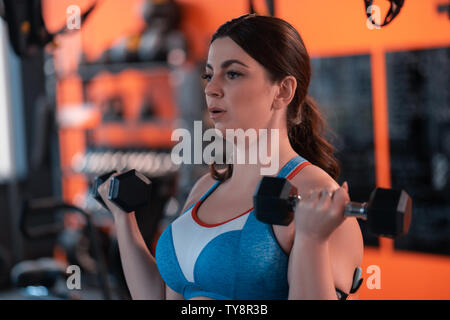 Mature woman working out in gym using barbells - Stock Photo