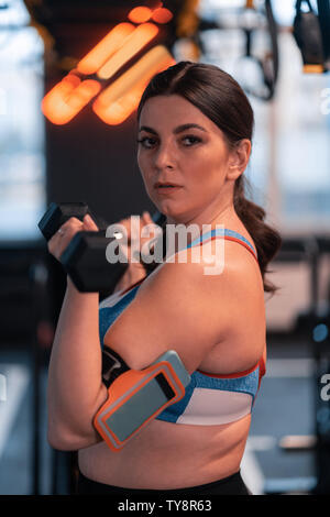 Dark-haired woman with overweight working out in gym - Stock Photo