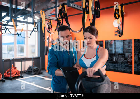 Trainer helping woman cycling in gym with speed mode - Stock Photo