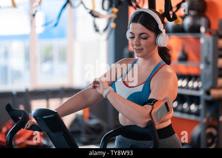 Woman in earphones checking calories on fitness tracker - Stock Photo