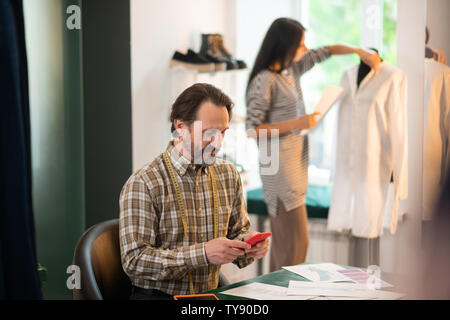 Handsome attractive handsome dark-haired adult designer clicking on the phone - Stock Photo