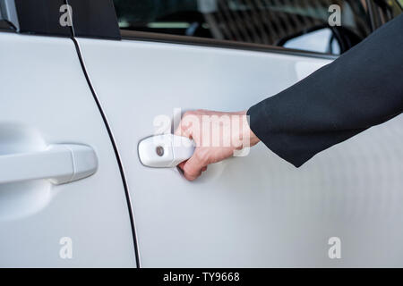 Formal hand on handle opening a white car door - Stock Photo