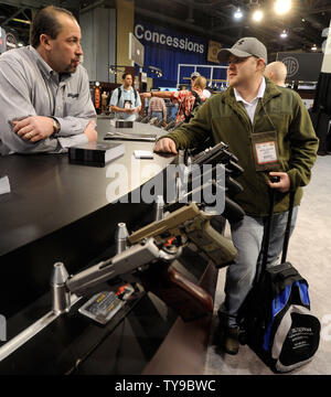 Hand guns are on display at the Sig Sauer booth at the National Shooting Sports Foundation's 35th annual Shooting, Hunting, Outdoor Trade (SHOT) Show at the Sands Expo and Convention Center January 16, 2013 in Las Vegas. The SHOT Show is the largest annual gathering of shooting professionals with more than 1,600 exhibitors and 60,000 attendees expected.  UPI/David Becker - Stock Photo