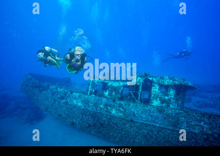 Two female divers (MR) on underwater scooters on the wreck of the Saint Anthony, off Maui, Hawaii. - Stock Photo