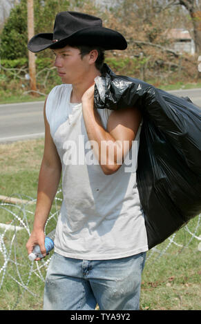 Scott Albritton of Wiggins, MS, picks up trash along the railroad tracks while working to install over 30 miles of concertina razor wire in the aftermath of Hurricane Katrina on Wednesday, Sept. 14, 2005 in Long Beach, MS.  (UPI Photo/Billy Suratt) - Stock Photo