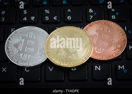 Three bitcoins on black keyboard of laptop - Stock Photo