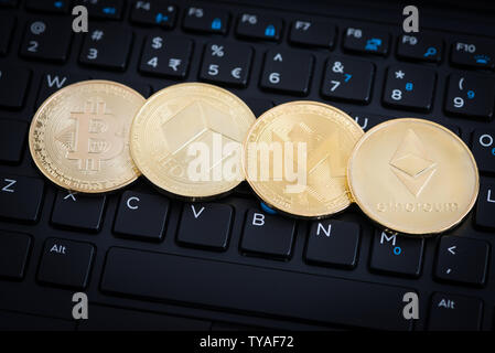 Four golden crypto currency coins - Bitcoin, NEO, Monero, Ethereum on black keyboard of laptop - Stock Photo