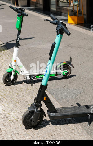 Berlin, Germany - June, 2019: Electric scooters , escooter or e-scooter on sidewalk in Berlin, Germany - Stock Photo