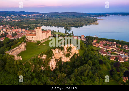 View of the fortress called Rocca di Angera during a spring sunset. Angera, Lake Maggiore, Varese district, Lombardy, Italy. - Stock Photo