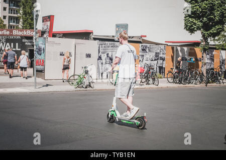 Berlin, Germany - June, 2019: Young man riding electric scooter , escooter or e-scooter on street  in Berlin, Germany - Stock Photo