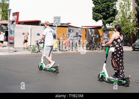 Berlin, Germany - June, 2019: Man and woman on electric scooter , escooter or e-scooter on street in Berlin, Germany - Stock Photo