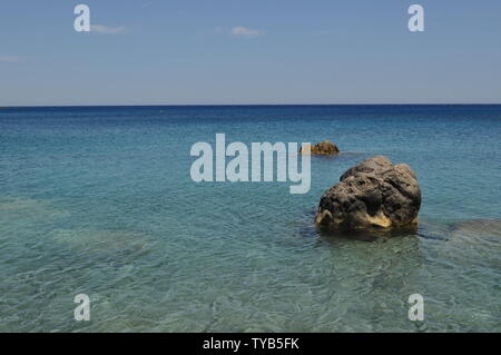 Crystal clear ocean of Karpathos, a small greece island in the aegean sea. - Stock Photo