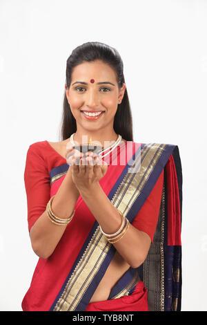 Portrait of a woman holding diya - Stock Photo