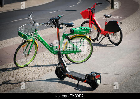 Berlin, Germany - June, 2019: Bike sharing bicycles and electric scooter , escooter or e-scooter on sidewalk in Berlin, Germany - Stock Photo