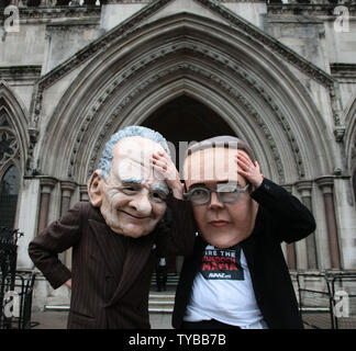 Protesters from the campaign group 'Avaaz' demonstrate outside the High Court with large James and Rupert Murdoch masks as former News International Chairman James Murdoch gives evidence to the Leveson Inquiry in London on Tuesday April 24 2012.The Leveson Inquiry is currently concentrating on the owners of various media groups. Rupert Murdoch,owner of News Corp will be giving evidence to the Inquiry tomorrow.     UPI/Hugo Philpott - Stock Photo
