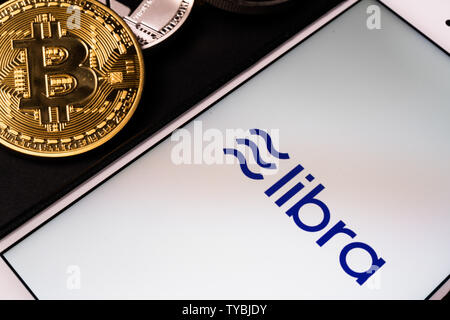 26 June 2019, Wuhan China: Libra the Facebook cryptocurrency logo on mobile phone screen and real coins of other crypto such as Bitcoin next to it - Stock Photo