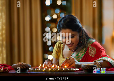 Woman decorating the house with diya on the occasion of diwali - Stock Photo