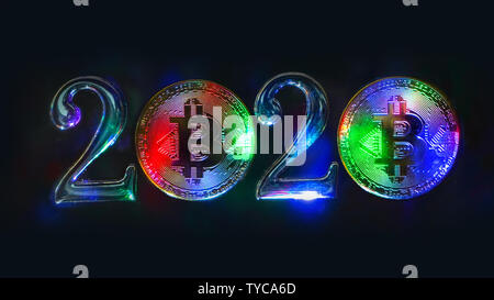 The concept of 2020 on the topic of cryptocurrency. Multi-colored bitcoin coins stand next to the numbers 2. Black background. - Stock Photo