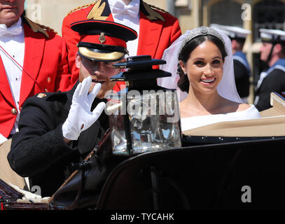 Prince Harry and his wife Meghan Markle leave in the Royal carriage from St George's Chapel in Windsor Castle in Windsor, England on May 19, 2018.   The couple have been bestowed the royal titles of Duke and Duchess of Sussex on them by the British monarch.    Photo by Hugo Philpott/UPI - Stock Photo