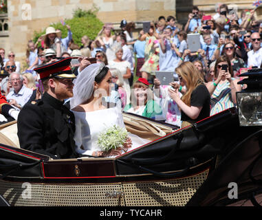 Britain's Prince Harry and his wife Meghan Markle leave St George's Chapel by carriage after their royal wedding ceremony, in Windsor, England, on May 19, 2018. The couple has been bestowed the royal titles of Duke and Duchess of Sussex on them by the British monarch. Photo by Hugo Philpott/UPI - Stock Photo