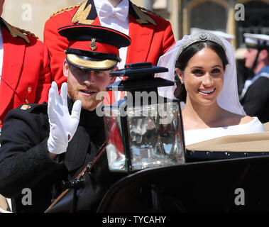 Prince Harry and his wife Meghan Markle leave in the Royal carriage from St George's Chapel in Windsor Castle in Windsor, England on May 19, 2018. The couple has been bestowed the royal titles of Duke and Duchess of Sussex on them by the British monarch. Photo by Hugo Philpott/UPI - Stock Photo