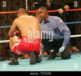 Referee Ken Bayliss counts over Trinidad Mendoza of Tijuana Mexico in the 6th round of his fight with Featherweight champion Adam Carrera of Cathedral City CA at the Orleans Casino in Las Vegas on November 19, 2004. Carrera won by decision. (UPI Photo/Roger Williams) - Stock Photo