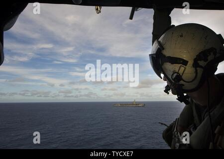 PACIFIC OCEAN (Oct. 31, 2016) Petty Officer 3rd Class Conner Luz watches as the aircraft carrier USS Carl Vinson (CVN 70) transits the Pacific Ocean during a photo exercise flight. Carl Vinson is underway conducting Composite Training Unit Exercise (COMPTUEX) off the coast of Southern California. - Stock Photo