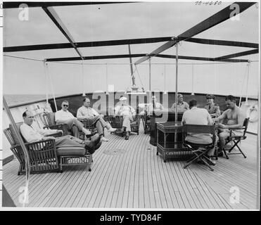 Photograph of President Truman and members of his party relaxing on the after deck of the presidential yacht, the U.S.S. WILLIAMSBURG, during a vacation cruise to Key West, Florida: (left to right) David Stowe, Administrative Assistant to the President; John Steelman, Assistant to the President; Charles Murphy, Special Counsel to the President; President Truman; Admiral Robert Dennison, Naval Aide to the President; Press Secretary Charles Ross; General Harry Vaughan, Military Aide to the President (back to camera); Commander Donald MacDonald, commanding officer of the WILLIAMSBURG; Gen. Robert - Stock Photo