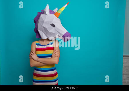 Young, creative girl holding on head 3D white unicorn head, posing on blue background in studio. Slender, stylish model standing in striped dress holding crossed hands. - Stock Photo