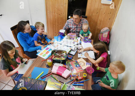 25 June 2019, Saxony, Schönwölkau: With five of their six children, Emma (2nd from left) and Stefan Fenchel (M) sit at a large table reading and doing handicrafts. The Bavarian and the Canadian moved to Leipzig in 2004 and now live in Schönwölkau with their six children, three girls and three boys between 12 and one year old. In the small village they have built an old house and enjoy the country life with their children. While at school in the neighboring city the German language is of course spoken, the whole family speaks English at home. (to dpa 'Where the children rich in Germany live - a - Stock Photo