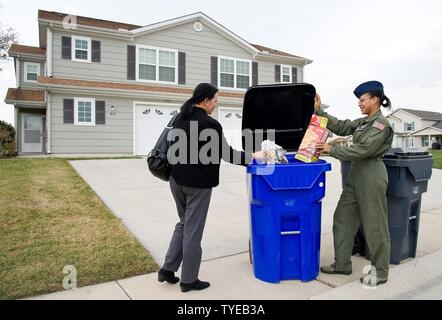 Sophia Reeves, Hunt Companies, Inc., Eagle Heights at Dover community director and Staff Sgt. Rachel Patterson, 3d Airlift Squadron loadmaster, place items in a 96-gallon recycle container Nov. 3, 2016, in Eagle Heights housing area on Dover Air Force Base, Del. In addition to curb-side recyclable pick up, two roll-off bins located at the Housing Maintenance office, building 3720 on Pine Cabin Road are available to Eagle Heights residents for bulk items such as furniture and a bin for metal items. - Stock Photo