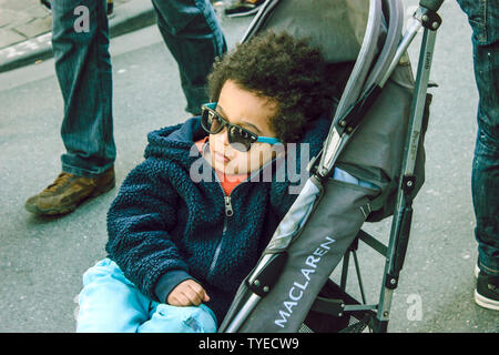 June 2019, Bruxelles, Belgium. Handsome and stylish wearing sunglasses in his pram/pushing chair. Cool cute black kid with blue sunglasses and curly h - Stock Photo