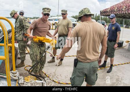 Chief Petty Officer Jesse Hamblin, center, assigned to Underwater Construction Team (UCT) 2's Construction Dive Detachment Bravo, moves a hydraulic tool in Diego Garcia, Nov. 4, 2016. CDDB is performing precision underwater demolition and light salvage to remove obstructions from Diego Garcia's deep draft wharf. CDDB is on the third stop of their deployment, where they are conducting inspection, maintenance, and repair of various underwater and waterfront facilities while under Commander, Task Force (CTF) 75, the primary expeditionary task force responsible for the planning and execution of co - Stock Photo