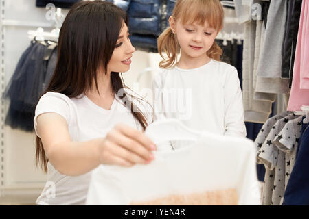 Selective focus of attractive brunette keeping new dress in hand and looking at daughter in store. Young woman choosing and buying clothes for little girl in shop. Concept of buying. - Stock Photo
