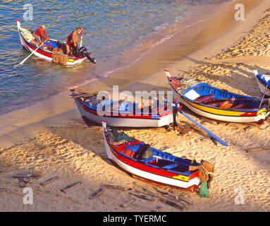 Aerial birds eye early view looking down from above colourful fishing boats on sandy beach Portuguese fisherman in boat at Carvoeiro Algarve Portugal - Stock Photo
